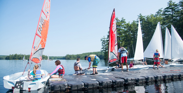 View of sail boats with open sails on dock at UNH Sailing Camp