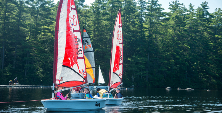 Two red sailboats on lake during UNH sailing camp