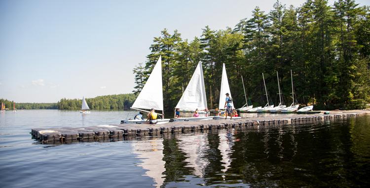 3 white sailboats on dock at UNH sailing camp