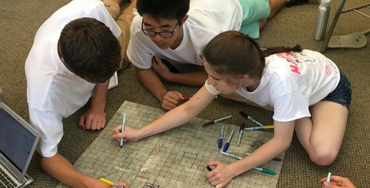 Upward Bound students on floor gathered around planning map