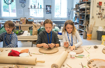Three students working with clay in art camp