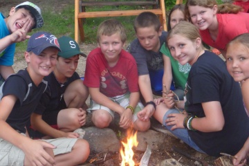 Campers gathered around a camp fire