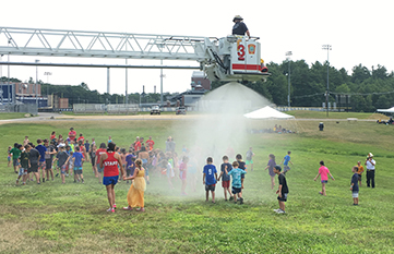Camp Wildcat Kids Having Fun with Fire Hose on Hot Summer Day